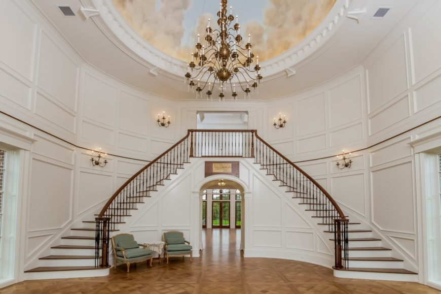 Upon entry of the house, you are welcomed by this grand foyer with a spacious hardwood flooring, dual staircase and a large chandelier hanging from a dome ceiling with a mural.