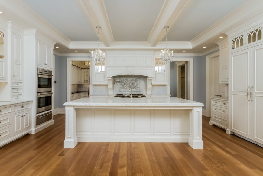 The kitchen has a large beige wooden kitchen island that pairs quite well with the hardwood flooring and pendant lights. Its tone also matches with the cabinetry surrounding it.