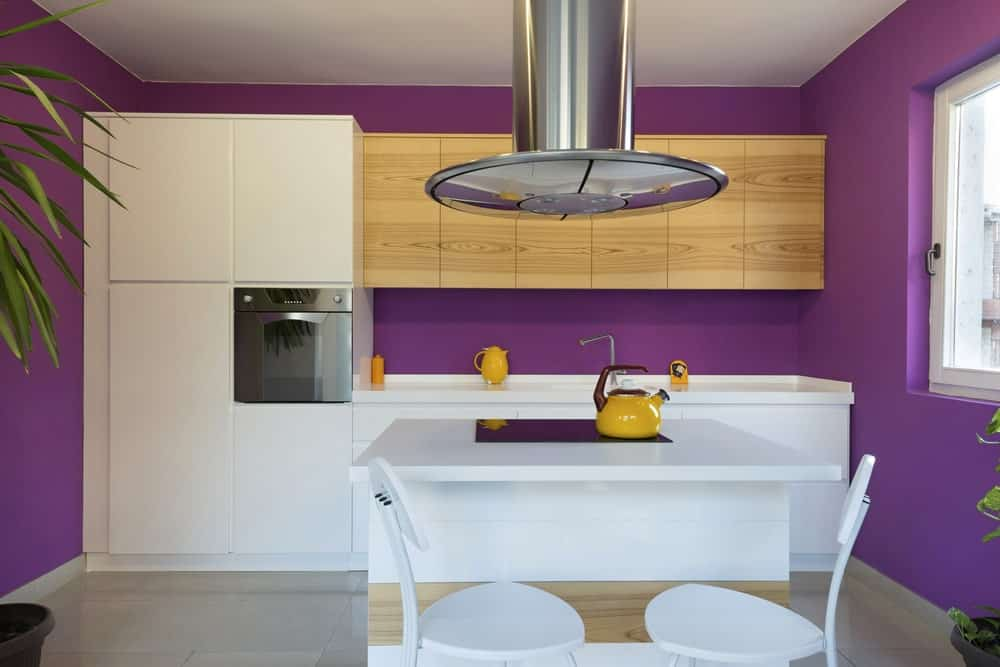 The lovely and cheerful purple walls of this small kitchen complements the white modern cabinetry against the wall paired with bare wooden floating cabinets above the sink area. This is paired with a small white kitchen island with a pair of white modern stools for the breakfast bar.