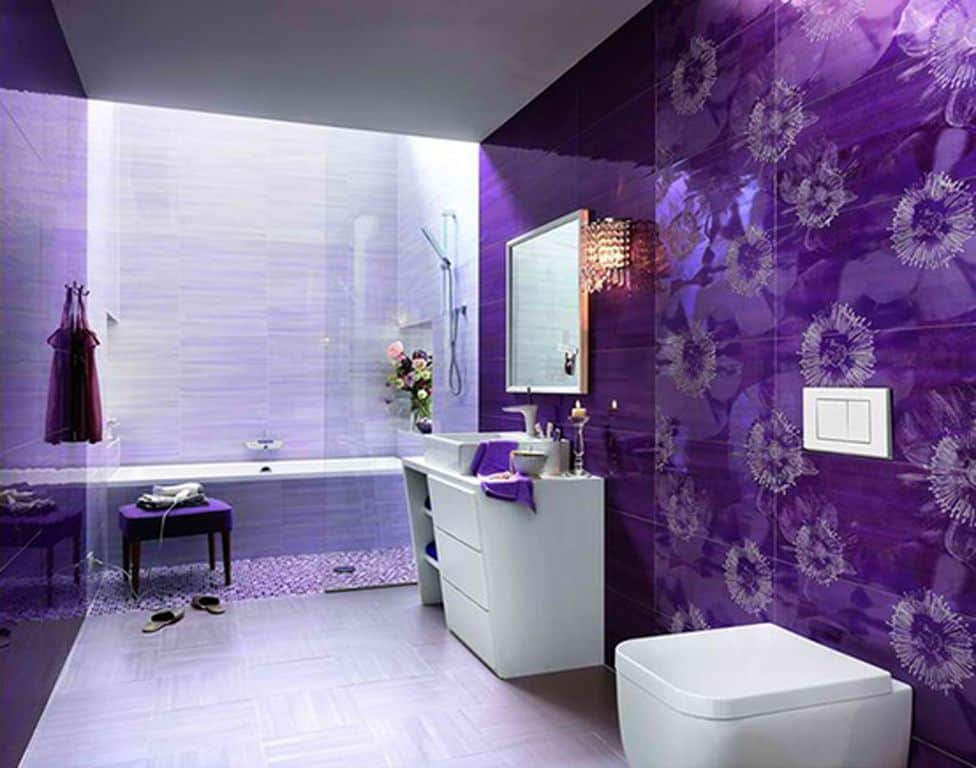 Modern primary bathroom with decorated purple walls. It has a stylish single sink counter with a vessel sink together with a shower and bathtub combo.