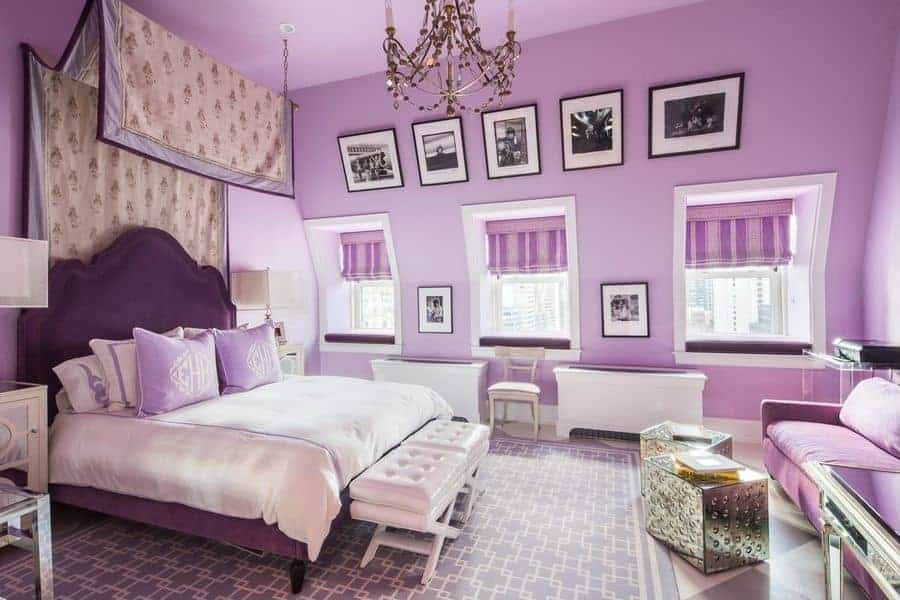 This purple primary bedroom is styled with a series of black framed photos and a gorgeous beaded chandelier that hung over the white tufted footstools. It showcases a sitting area and a charming upholstered bed with a canopy overhead.
