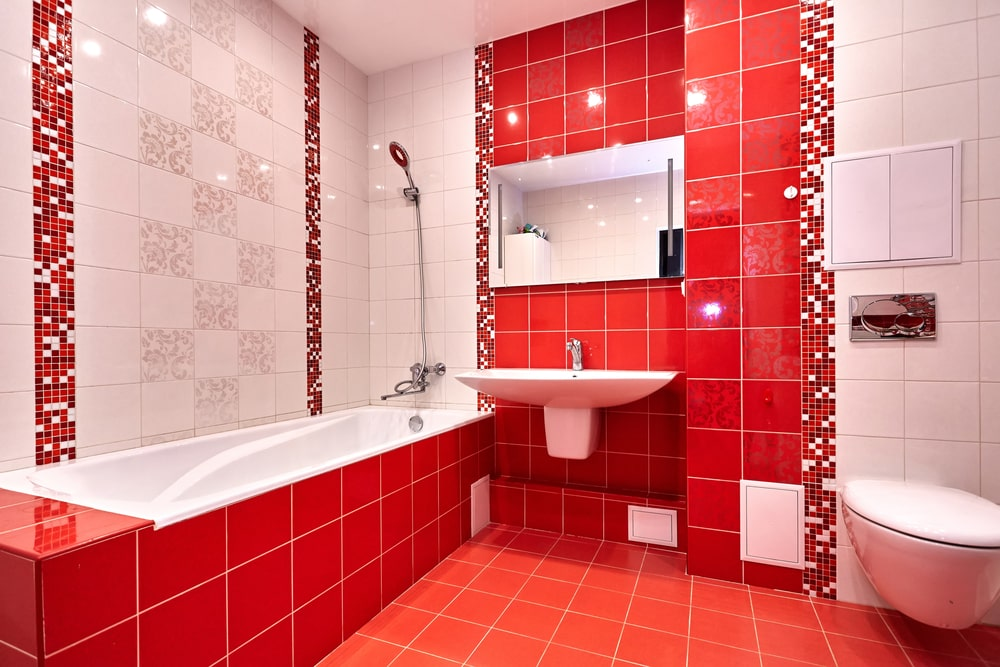 This primary bathroom features red tiles flooring and walls, along with a floating sink and a shower and tub combo on the side.