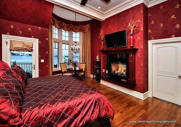This primary bedroom is clad in red patterned wallpaper that matches the luxury silk bedding. It showcases a fireplace with a TV on top along with a sitting area by the bay window dressed in classy drapes and valances.