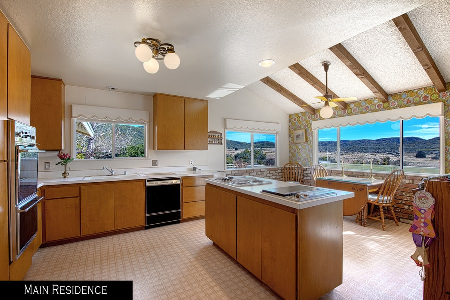 The kitchen has wooden cabinetry on its kitchen island that matches those lining the walls that house modern appliances. On the far side is an informal dining area by the wide windows.
