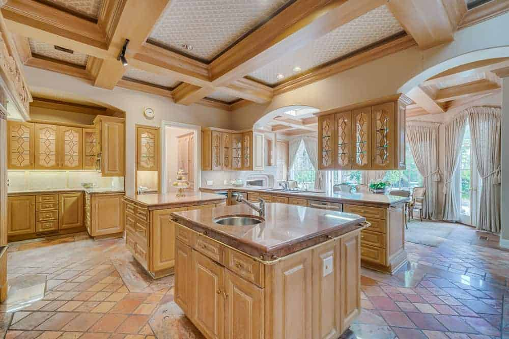 This is the large kitchen with enough space for two kitchen islands and a kitchen peninsula aside from the surrounding cabinetry of cabinets and drawers paired with earthy brown counters that go well with the terracotta flooring tiles.