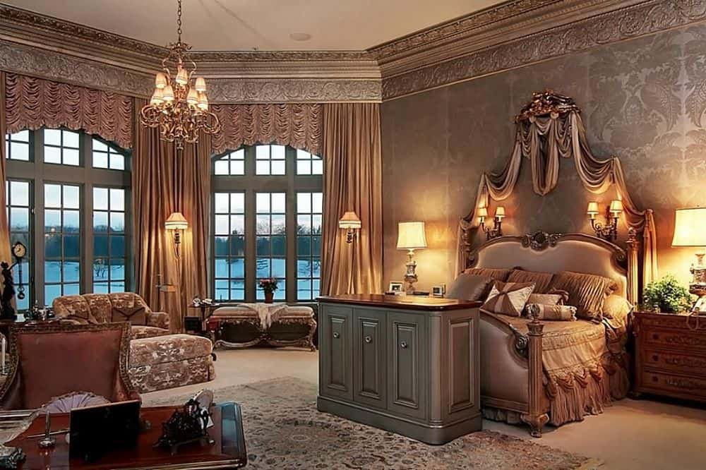 A stunning primary bedroom suite surrounded by elegant walls. The room offers a luxurious bed set and other furnishings. The room is lighted by wall lights, table lamps and a gorgeous chandelier.