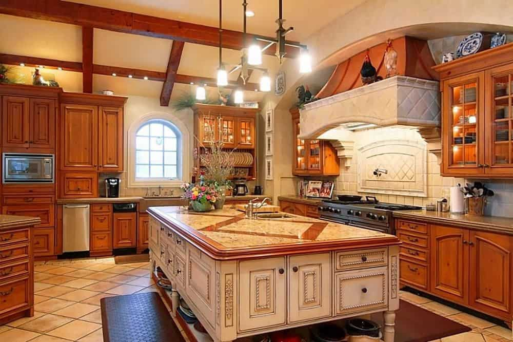 Large kitchen with a massive center island with a custom and elegant-looking countertop, lighted by charming ceiling lights.