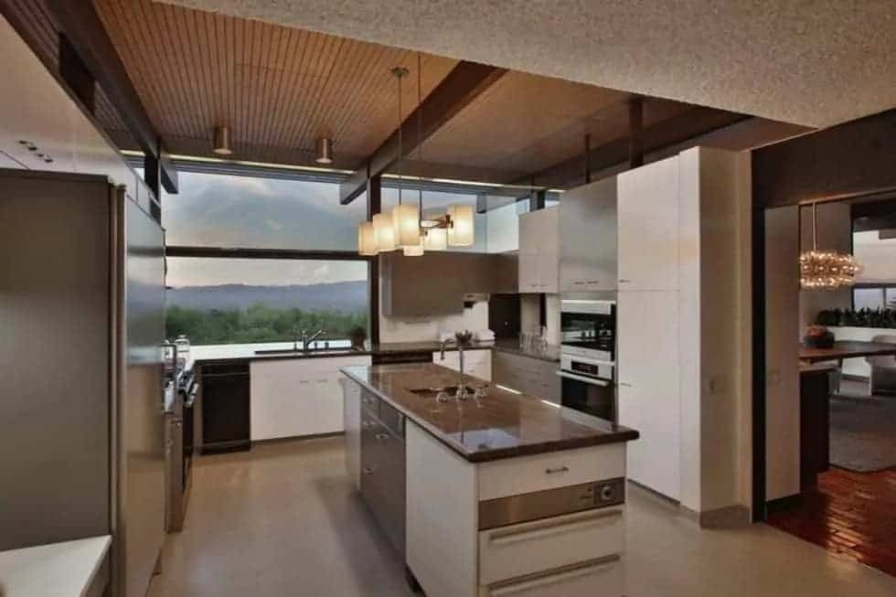 The kitchen has a dark tone to the countertops of the kitchen island and the surrounding cabinetry. These pair well with the stainless steel appliances as well the beams of the ceiling.