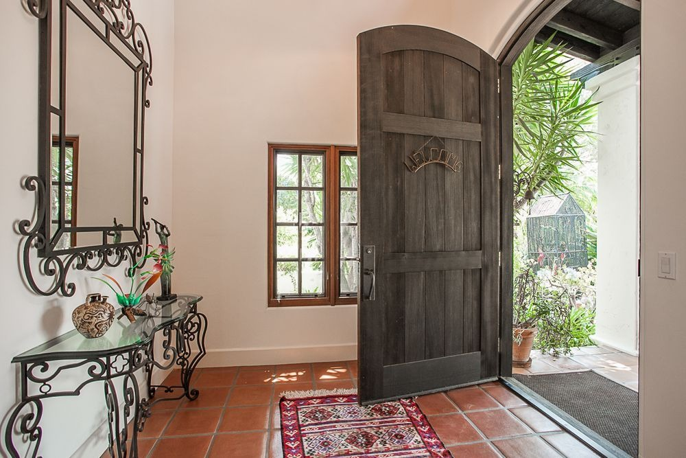 This entry has a rustic door and terracotta floors, along with white walls.