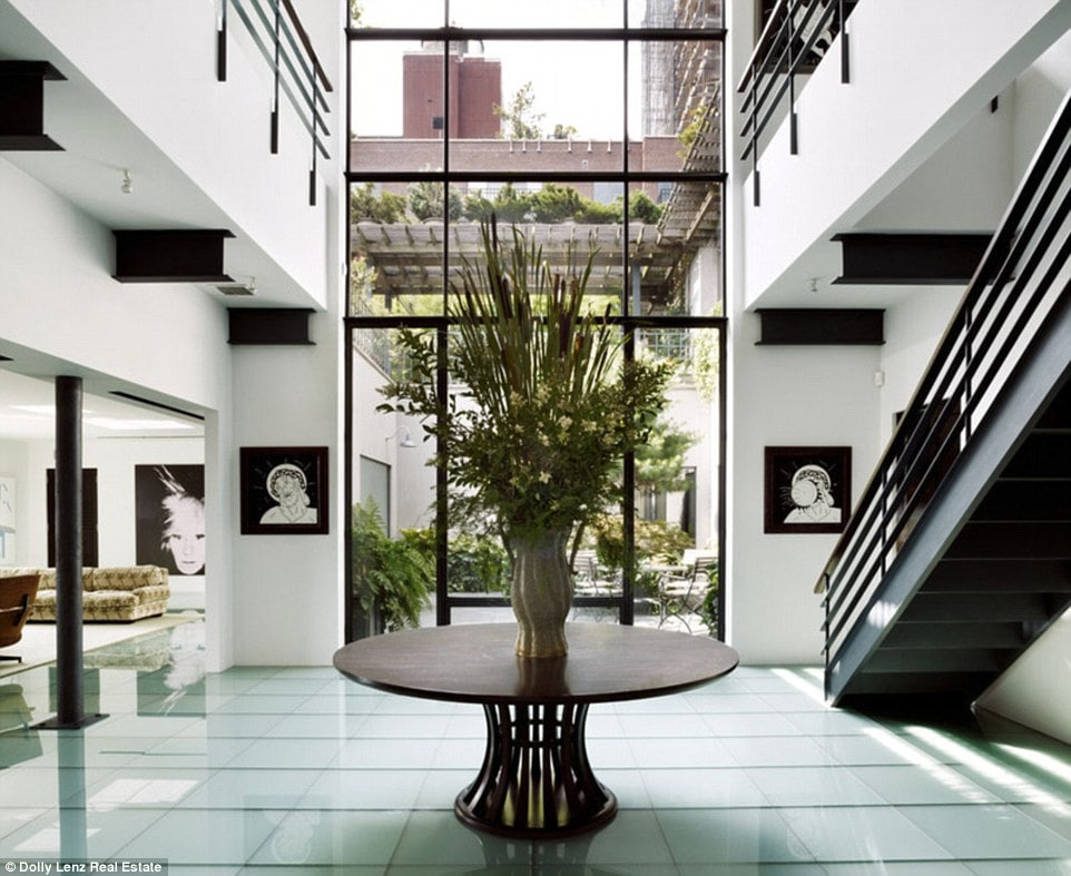Upon entry of the penthouse, you are welcomed by this foyer with a dark round table brightened by tall white walls and a large glass wall on the far side that brings in natural lighting.
