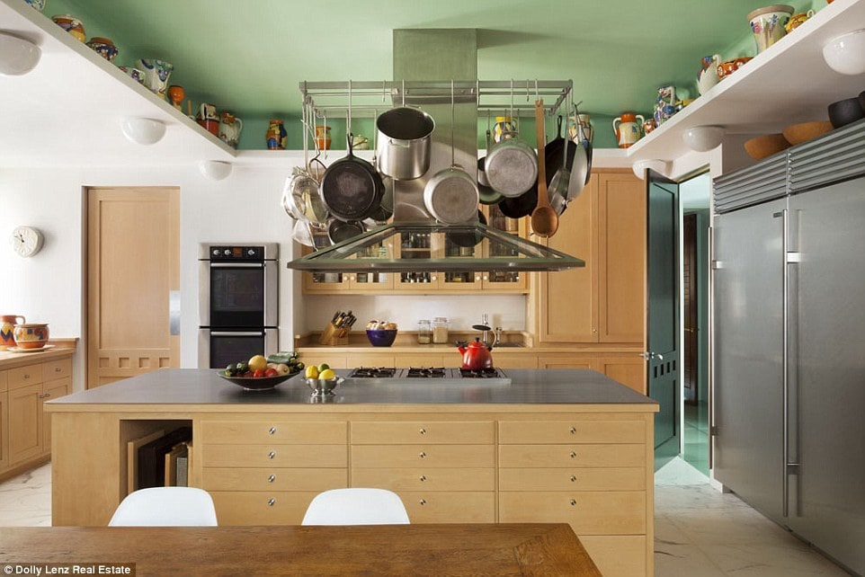 This is the eat-in kitchen with a wooden kitchen island topped with a pot rack hanging from a green tray ceiling.