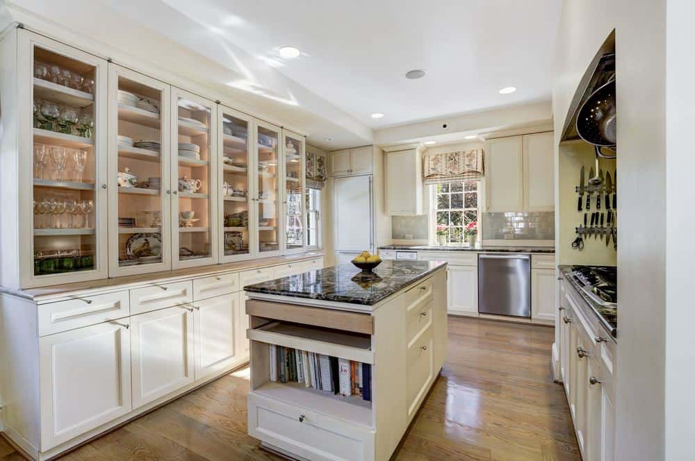 This is the kitchen that has a small kitchen island in the center of the hardwood flooring. This matches with the cabinetry that dominate the walls of this bright kitchen.