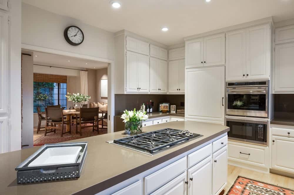 This kitchen area features white kitchen cabinetry and drawers, along with a gray kitchen countertop.