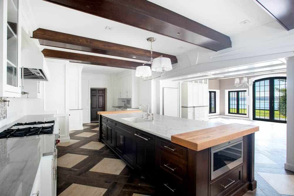 This is a close look at a kitchen that has dark wooden tones on the exposed beams of the ceiling, patterned flooring tiles and large kitchen island that has a white countertop.