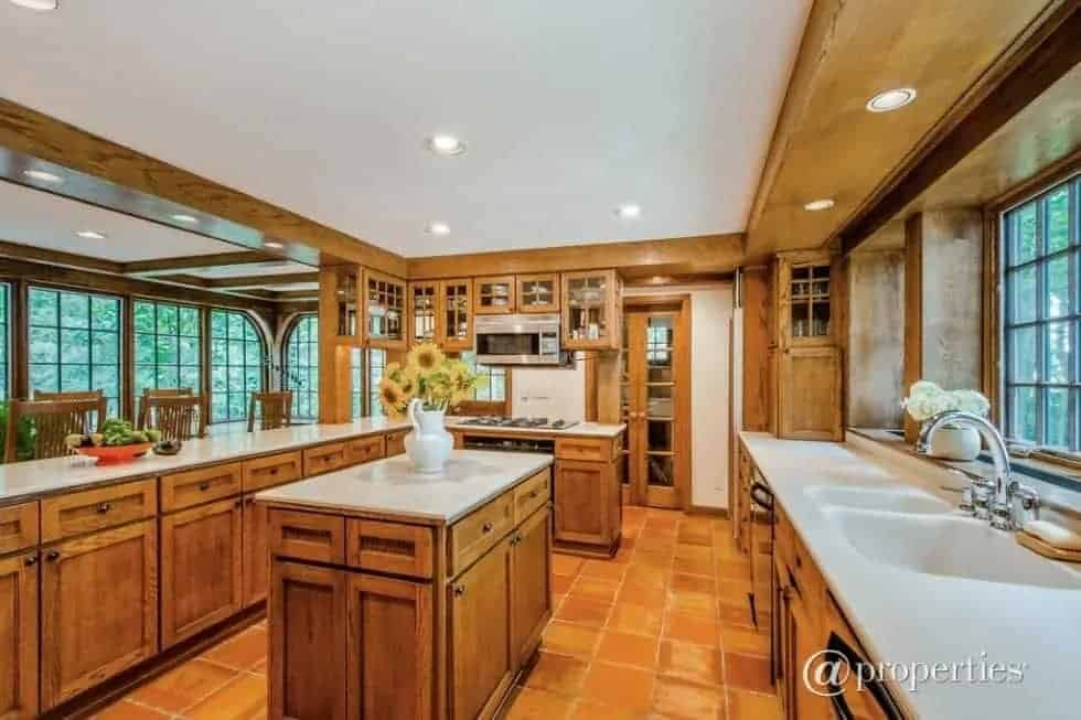 The kitchen terracotta flooring tiles match well with the wooden kitchen island and surrounding cabinetry complemented by the light-toned counters.