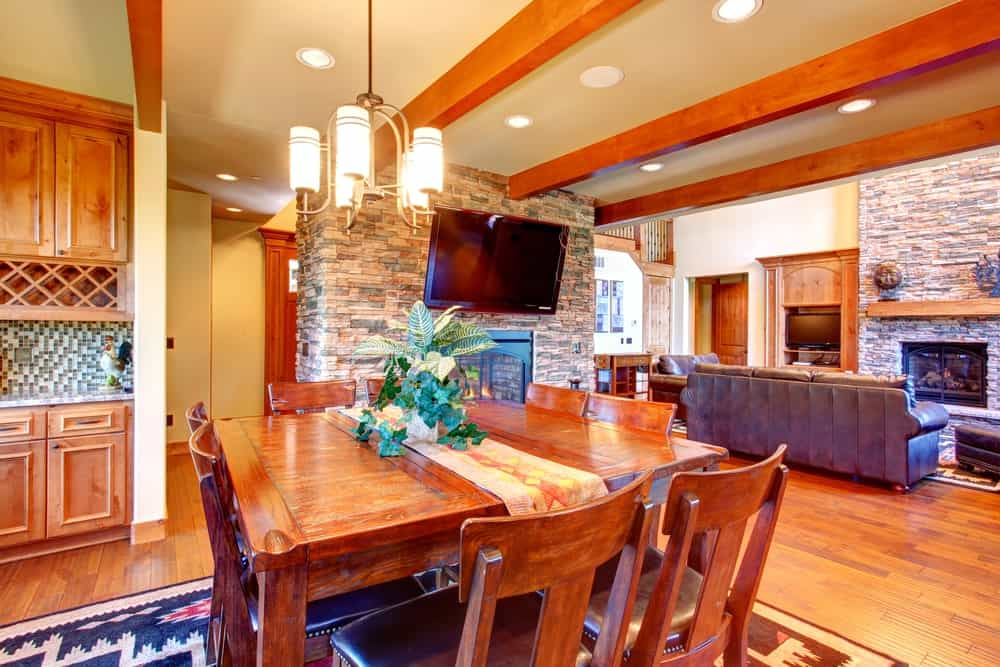 An open concept house with a cozy dining space behind the living room featuring a patterned area rug and wooden dining set that blends in with the hardwood flooring.