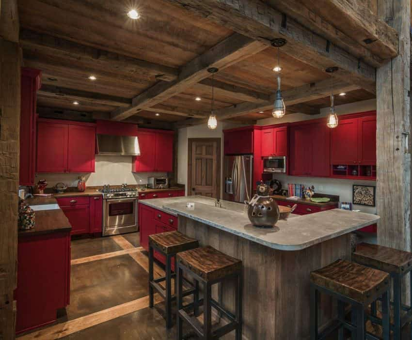 The rustic wooden ceiling of this charming and homey kitchen presents a nice wooden complement to the red matte cabinetry of the L-shaped kitchen cabinetry that has a wooden countertop as well as the built-in desk at the corner near the gray concrete breakfast bar.
