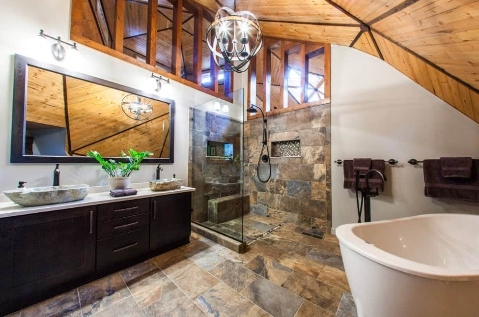 Primary bathroom with a rustic ceiling and tiles floors. It offers a sink counter with two vessel sinks, along with a large freestanding soaking tub and a walk-in shower area.
