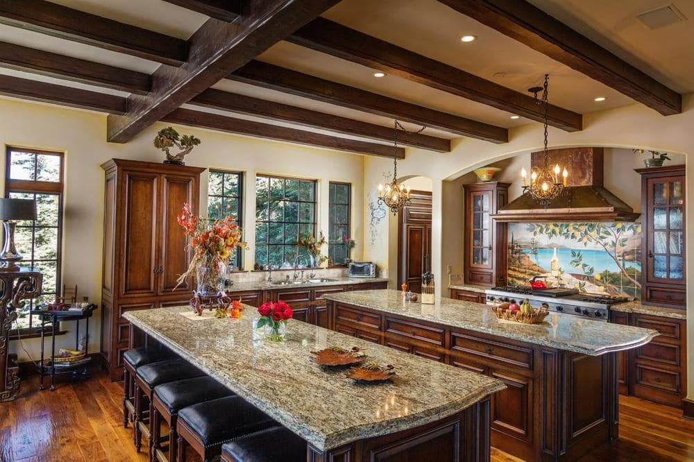 The spacious kitchen has enough space for two kitchen islands with the same marble countertop that contrasts the dark brown cabinetry.
