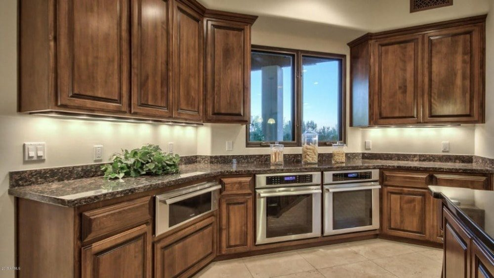 This is the kitchen that has dark brown tones on the cabinetry lining the walls. This is paired with black granite countertop and stainless steel appliances.