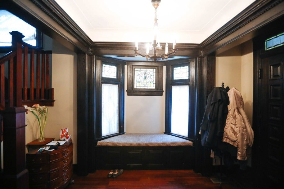 Upon entry of the house, you are welcomed by this foyer with a small chandelier and a built-in bench on the side by the window flanked by a coat rack and a wooden drawer.