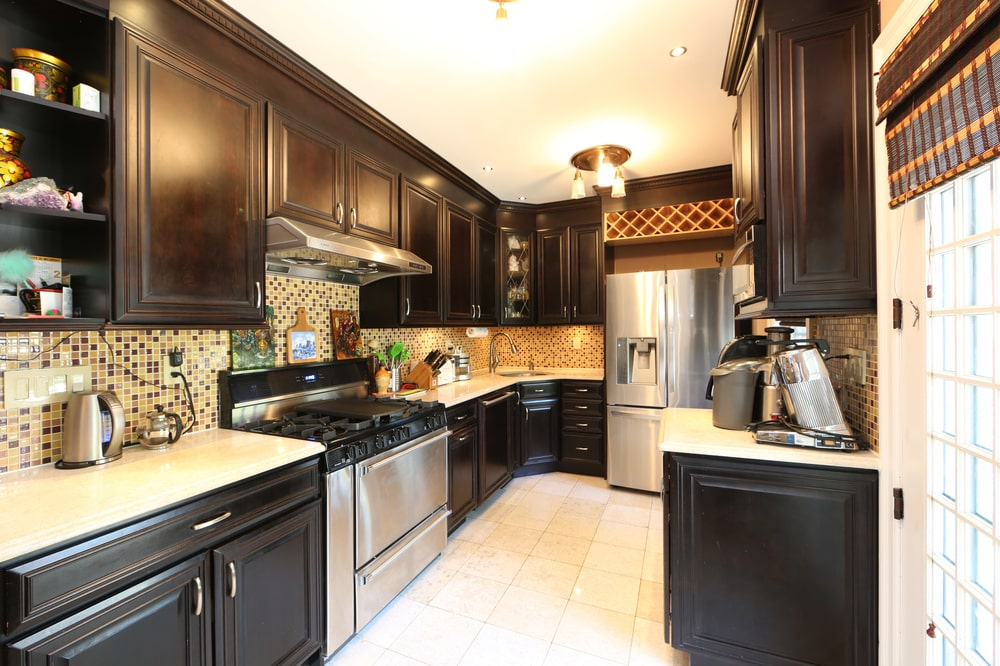 This is the kitchen with black wooden cabinetry lining the walls. These contrast the light beige tone of the countertops, ceiling and floor.