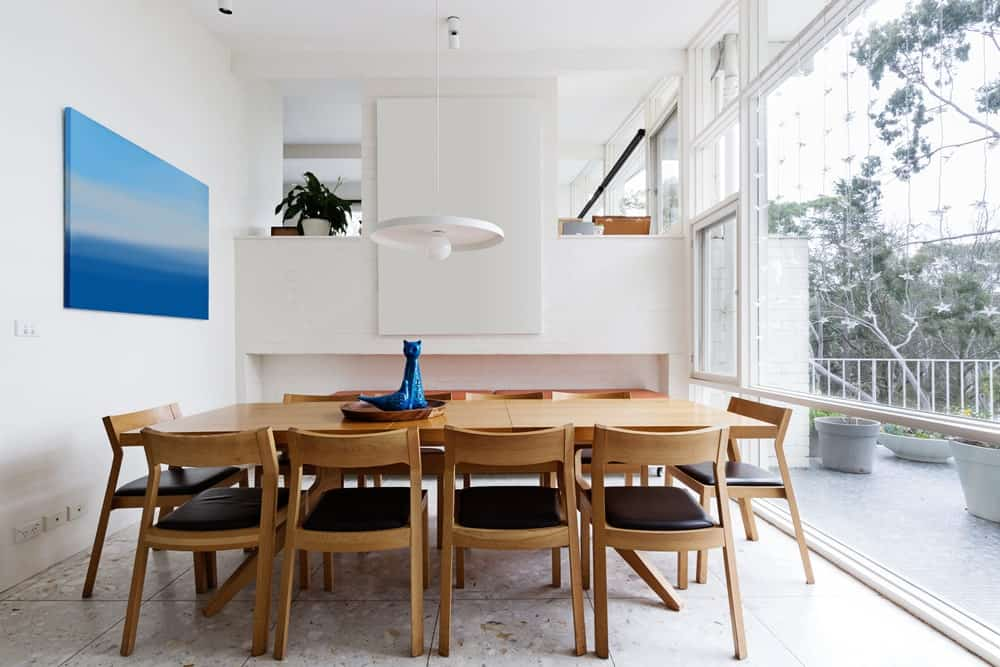 Full height glazing creates a sense of space in this bright dining room with tiled flooring and white walls accented by a blue canvas painting. It is filled with sleek cushioned chairs and a wooden dining table lit by a white pendant light.