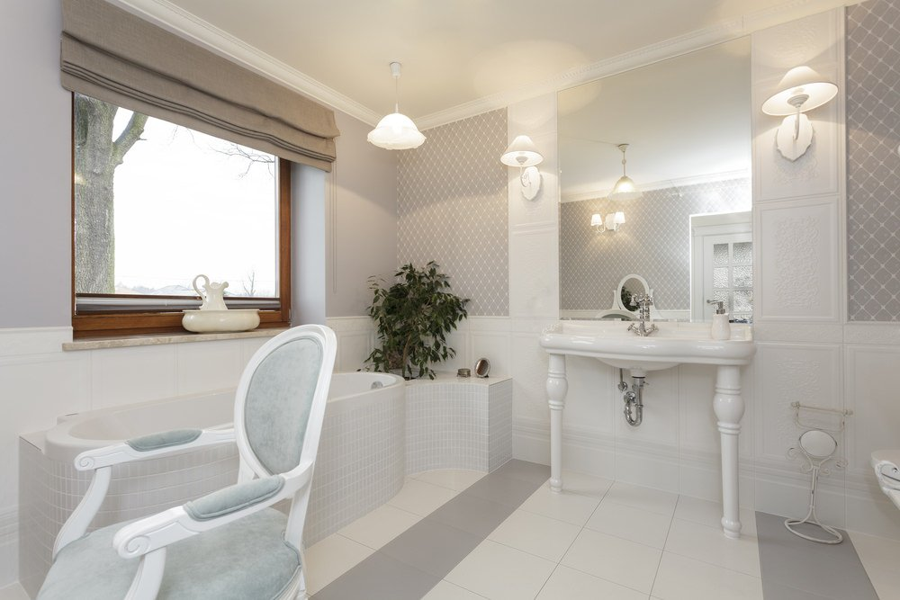 Scandinavian primary bathroom with tiles floors and gorgeous decorated walls. It features a deep soaking tub on the side and a sink counter lighted by classy wall lights.