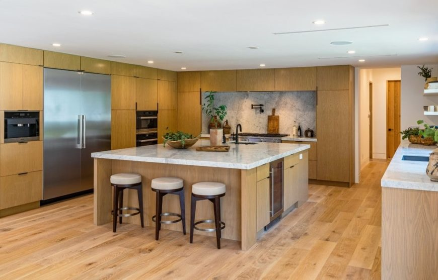 This is the spacious kitchen with a large square kitchen island in the middle with wooden cabinetry that blends with the hardwood flooring. These are then complemented by the white marble countertops and stainless steel appliances.