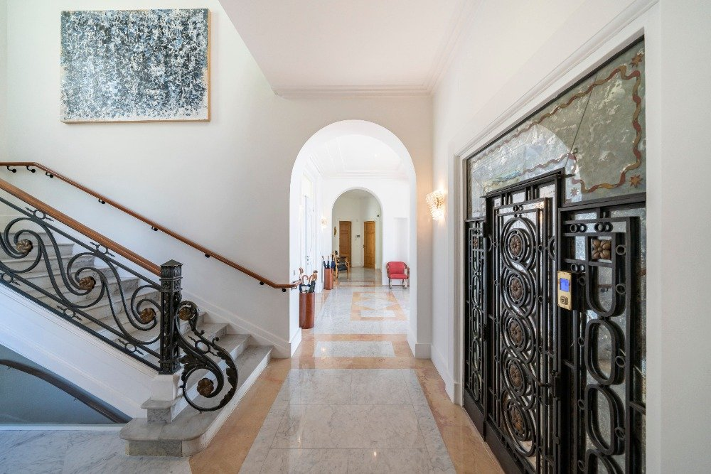 Entry foyer with classy tiles flooring and a gorgeous wide staircase with elegant railings.