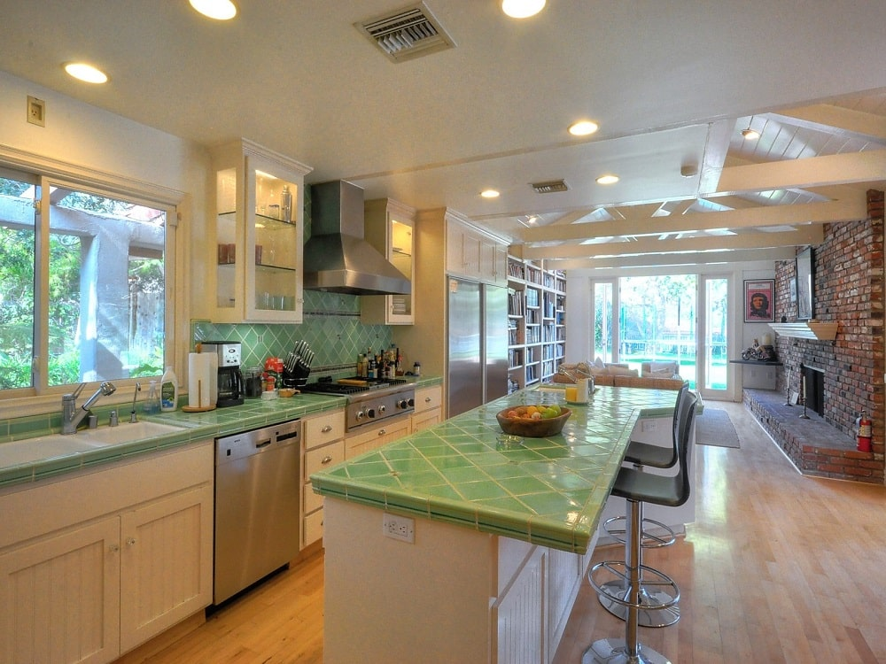 This is the kitchen with green tiles on the countertops of the kitchen island the cabinetry that has a beige tone to match the ceiling.