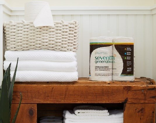 Seventh Generation toilet paper rolls on a storage area beside folded sheets of clean white linen.