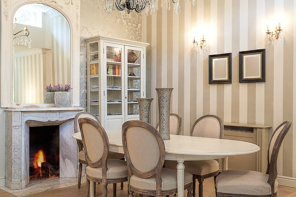 Clad in striped and fleur patterned wallpaper, this dining room showcases beige round back chairs and an oval dining table topped with lovely vases. It includes a display cabinet and a fireplace under a chic arched mirror.