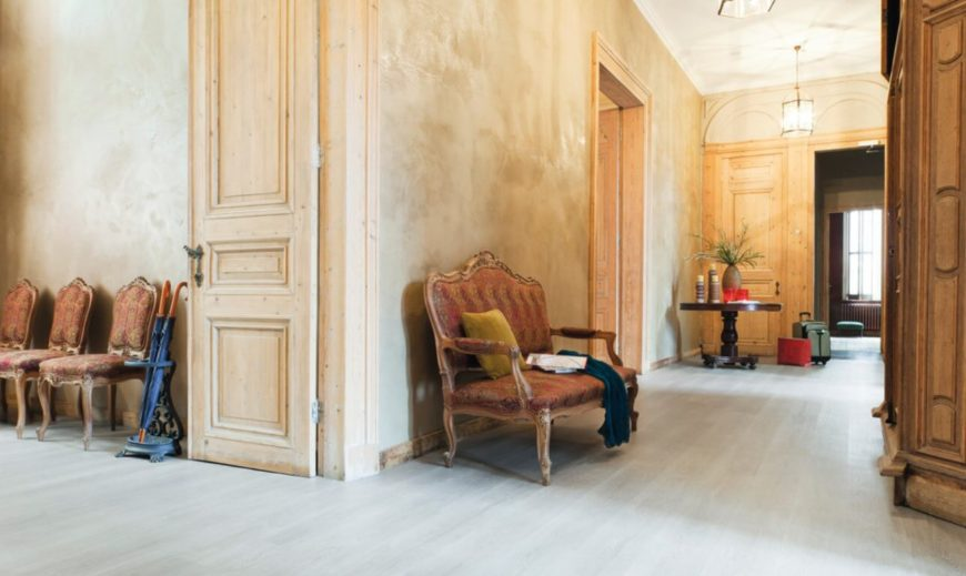 Shabby-chic style foyer with beige walls, whitewashed flooring, and distressed-looking furniture.