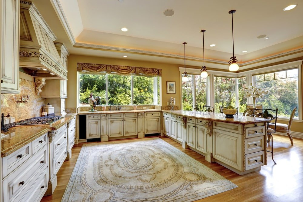 The distressed white shaker cabinets and drawers of the large U-shaped peninsula gives this shabby-chic kitchen a unique aesthetic matched with the large light patterned area rug in place of a kitchen island in the middle of the hardwood flooring.