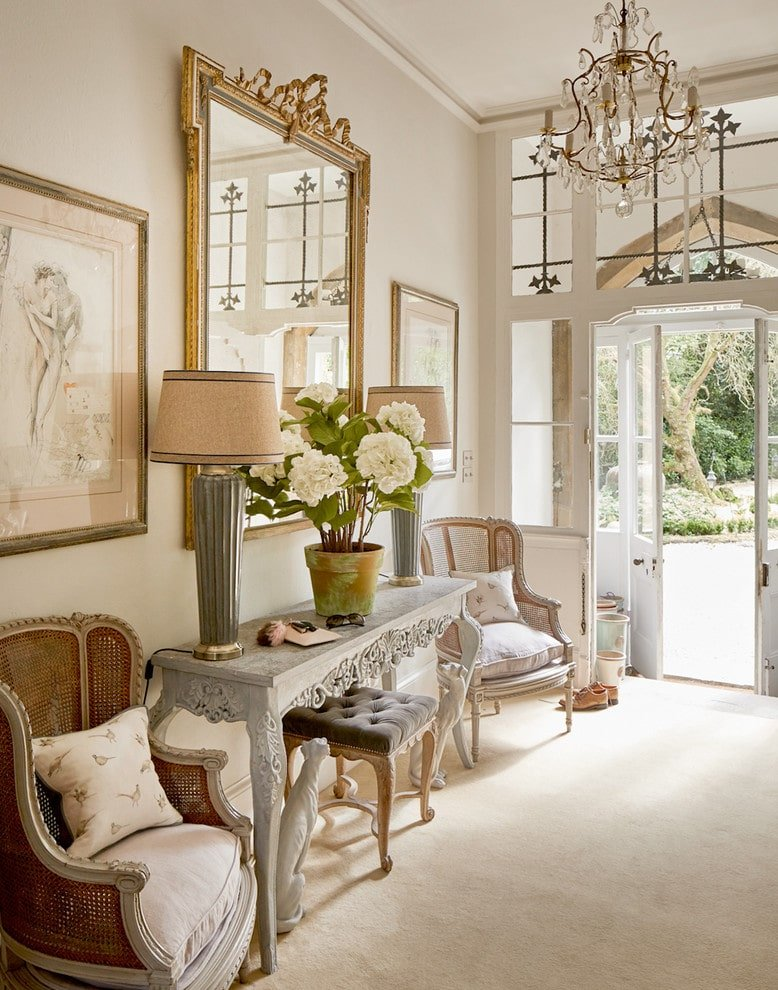 Upon entering this foyer through its French door, you will be greeted by wicker wingback chairs and a carved wood table with an elegant cushioned stool underneath. This room is decorated with a fabulous crystal chandelier and gorgeous artworks mounted on the clean, white wall.