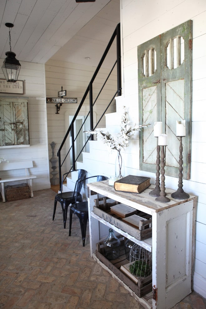 Shabby chic style foyer with shiplap walls and a brick flooring arranged in a herringbone pattern. It is furnished with contrasting black and white seats along with a distressed table filled with storage trays.