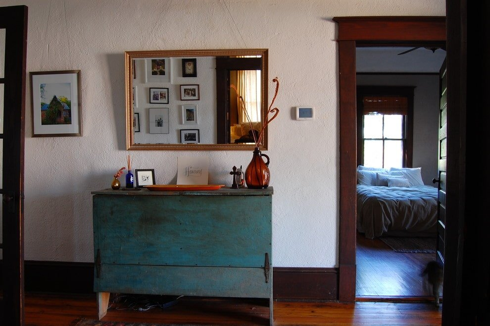 This entryway offers a large framed mirror and a blue console table that's topped with translucent vases and an orange flat bowl. It has rich hardwood flooring and white textured walls adorned by a wooden framed artwork.
