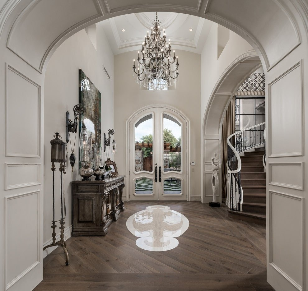 Luxury foyer with a gorgeous French door and open archways clad in white wainscoting. It is illuminated by eccentric sconces and a fabulous chandelier that hung from the high barrel vaulted ceiling.