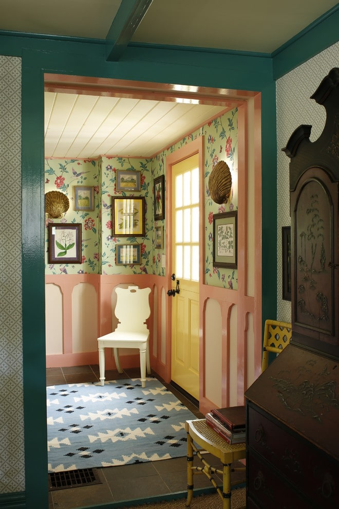 Clad in floral wallpaper and charming pink wainscoting, this foyer showcases gallery frames and shell sconces along with a white chair on a blue patterned rug over gray tiled flooring.