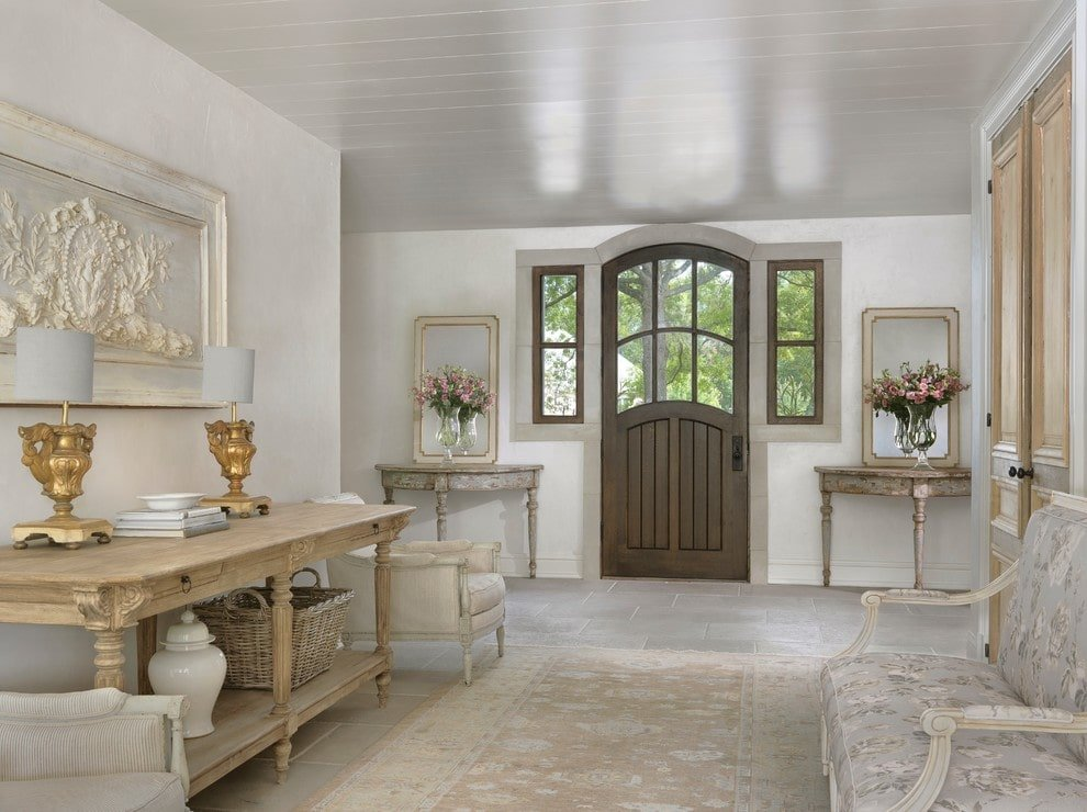 A pair of rustic tables with glass vases and mirrors on top flanked a dark wood entry door that's fitted with side glass panels and insets. This foyer is filled with cozy seats and a shabby chic rug along with a natural wood table that's highlighted by brass table lamps and a carved wood wall art.