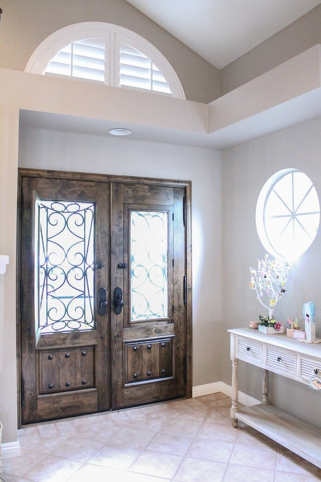 Shabby chic style foyer features a gorgeous wooden double door fitted with glass panels that are framed with ornate metals. It is accompanied by a louvered transom window and a round framed window fixed above the light wood console table against the light gray wall.