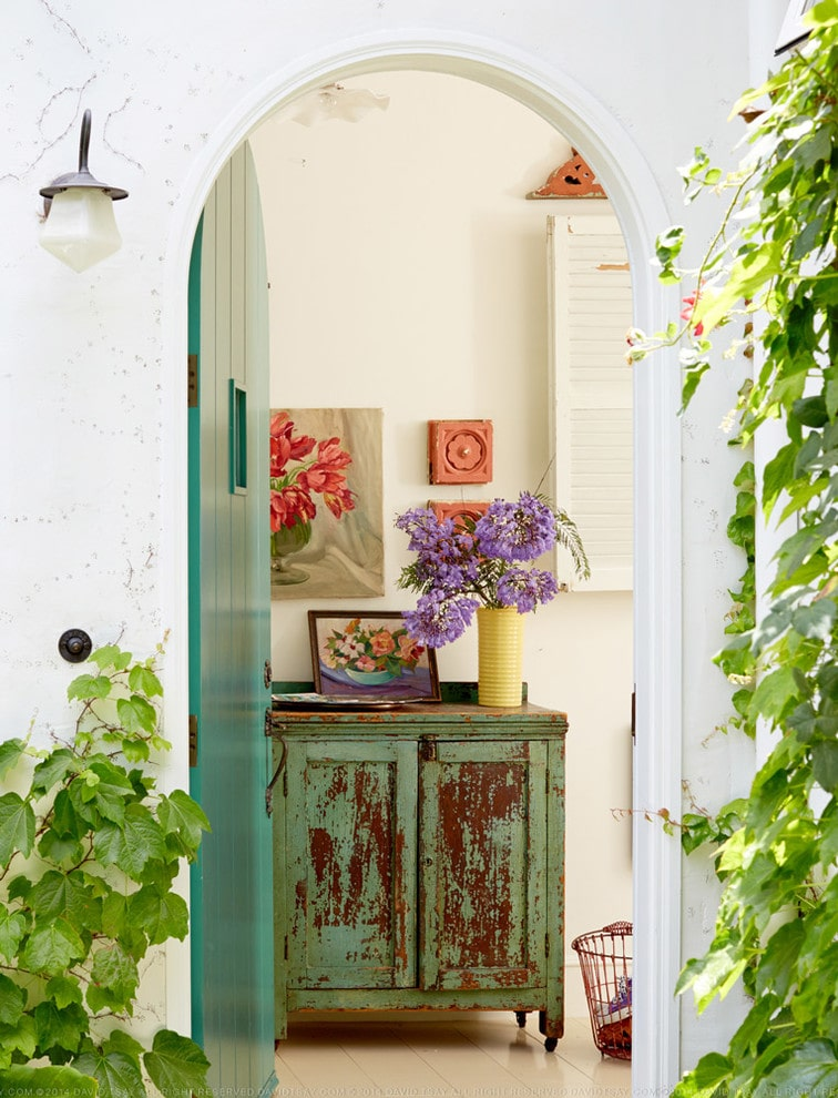 A green arched entry door accentuated by creeping plants opens to this foyer decorated with floral artworks and a yellow cylindrical vase that sits on a distressed console table over white tiled flooring.