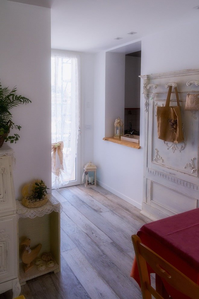 The narrow foyer features charming wood decors and a hook rack with ornate design. It has wide plank flooring and a glazed front door dressed in white lace curtain that's accented with a lovely ribbon.