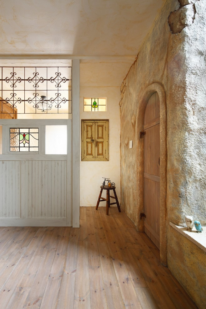 A marvelous stone wall sets a textured backdrop to the arched entry door that blends in with the wide plank flooring. It is accompanied by a round stool and a distressed white wall divider that's fitted with glass insets.
