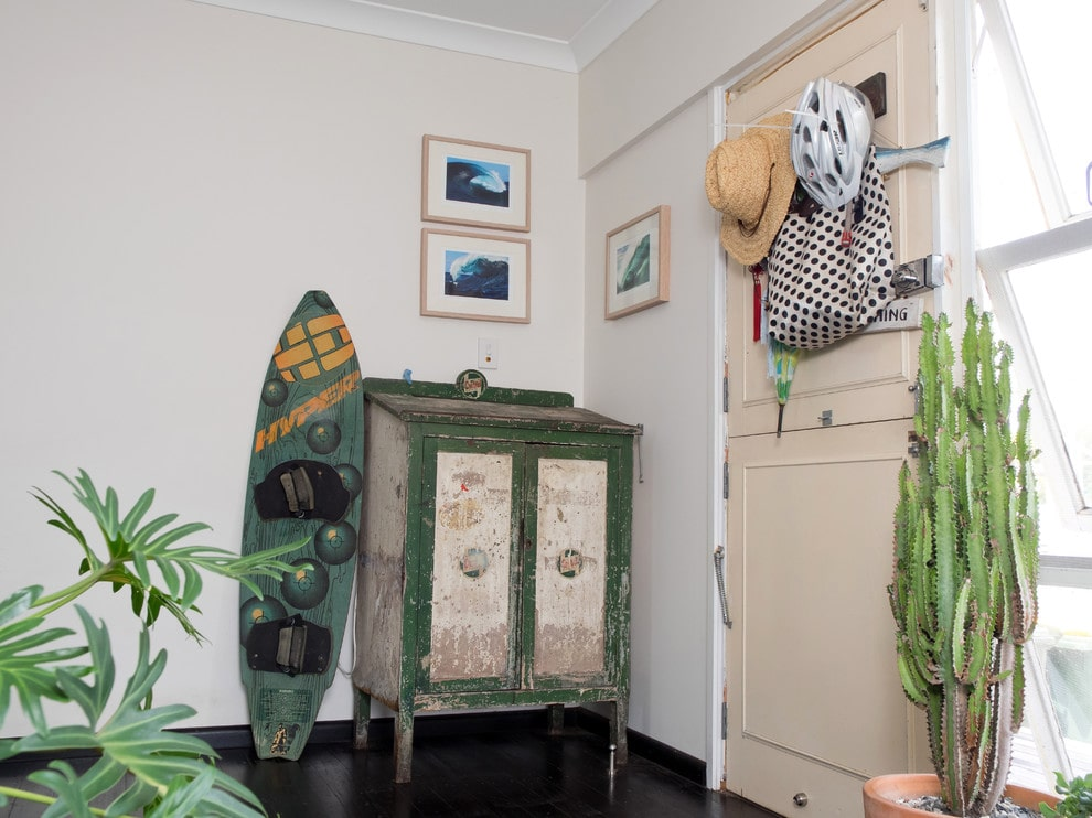 Shabby chic foyer showcases a beige front door and a distressed green cabinet with a printed skateboard on the side. It is decorated with ocean wave artworks and green potted plants that create a tropical feel in the room.
