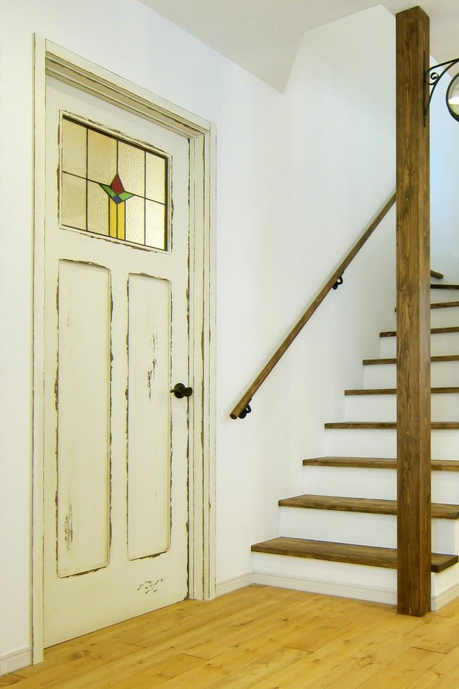 A small foyer supported with a natural wood column that's mounted with a wall sconce. It is filled with a traditional staircase and a distressed front door fitted with a stained glass panel and a wrought iron knob.