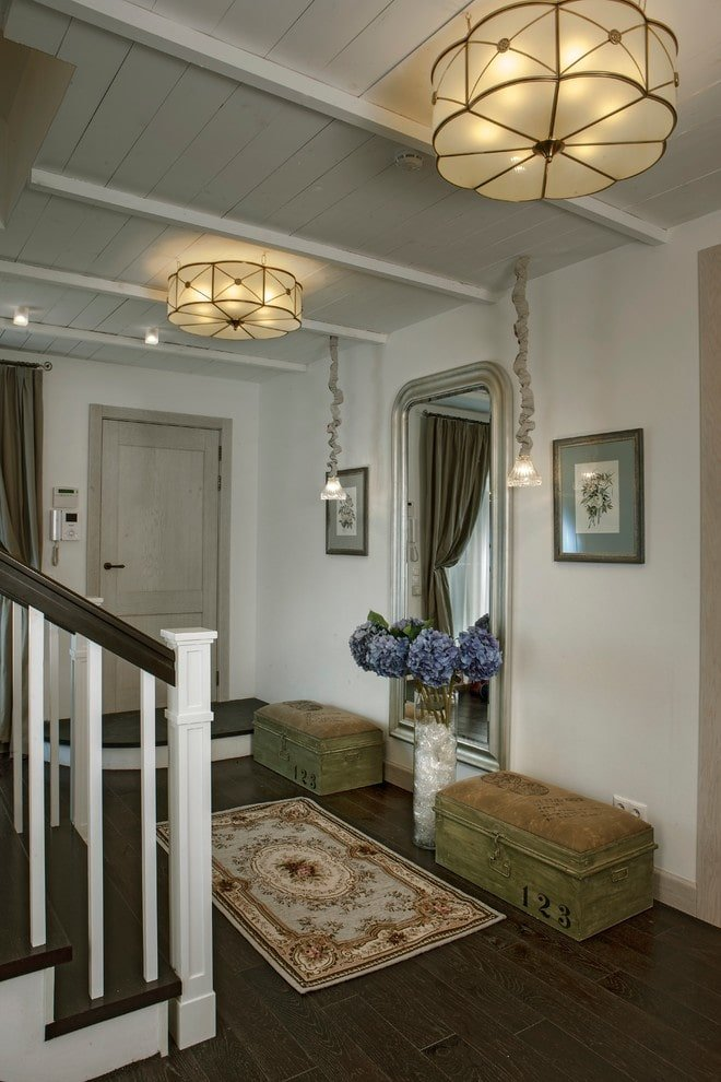 A pair of storage seats and floral artworks create perfect symmetry in this foyer with an arched full-length mirror and a charming area rug that lays on the dark hardwood flooring. It is illuminated by unique pendants and lovely flush mount lights.