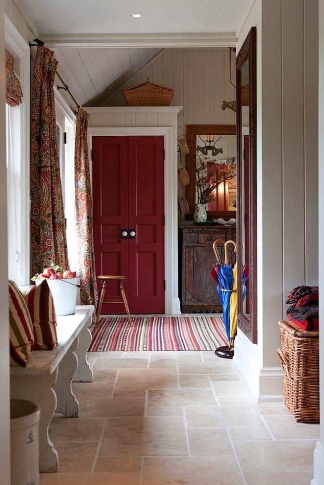 A red double entry door stands out in this foyer along with a striking striped rug that lays on the limestone flooring. It is furnished with a rustic console table, a round stool and a distressed white bench facing the full-length mirror that's mounted on the taupe beadboard wall.