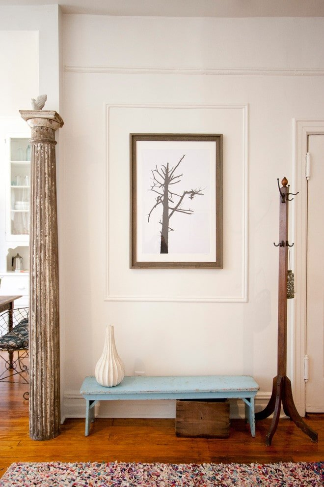 A sky blue bench flanked by a coat rack and distressed Greek column brings a pop of color in this foyer. It is decorated with a multi-colored rug, a gorgeous vase and a tree branch artwork framed in white trims.
